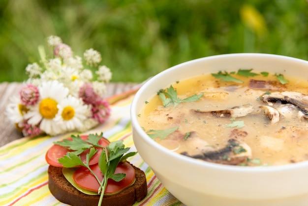 Sommer hühnersuppe mit pilzen und kräutern.