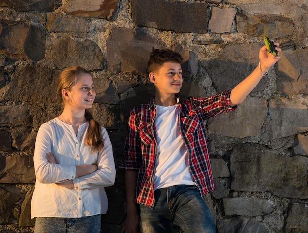 Sommer, kindheit, freizeitkonzept. glückliches lächelndes mädchen und junge, die selfies mit smartphone nahe steinmauer nehmen. sommer sonniger tag