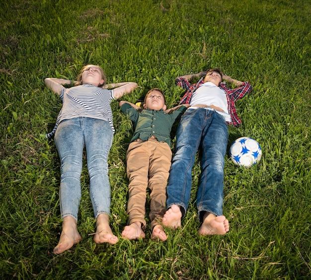 Sommer, kindheit, freizeitkonzept. gruppe glücklicher kinder, die auf dem gras liegen und sich nach dem spiel im park ausruhen.