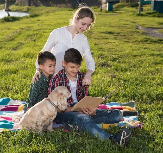 Sommer, kindheit, freizeitkonzept. kinder sitzen auf dem gras und lesen buch im park. sonniger sommertag