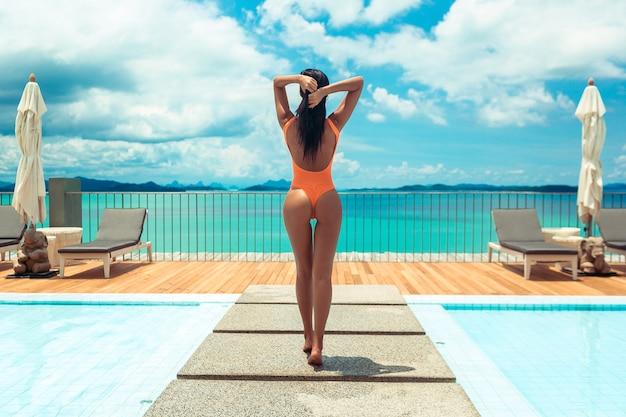 Sommer körper. frau im orange badeanzug nahe swimmingpool mit seeansicht. mädchen in der modernen badebekleidung mit perfektem körper am luxusresort. rückansicht