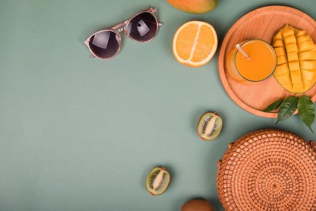 Sommer komposition. sonnenbrille mit mango, orange, kiwi auf grünem hintergrund