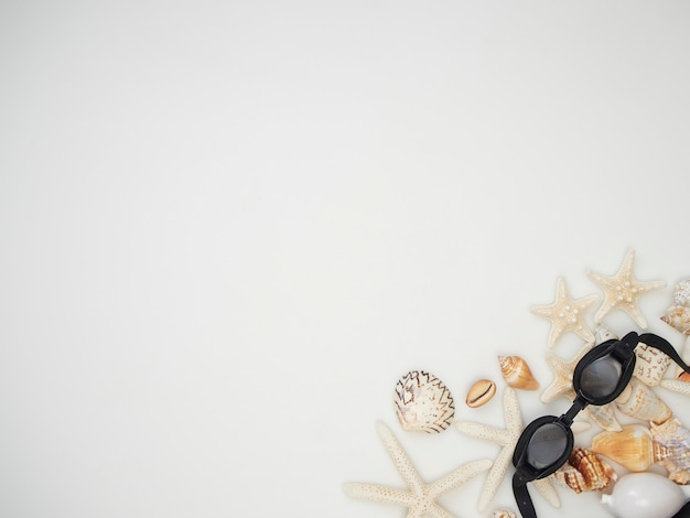 Sommer-konzept. muscheln, seesterne, schwimmende gläser auf einem weißen hintergrund