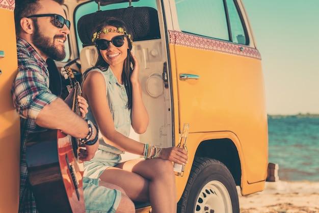 Sommer melodien. glückliches junges paar, das zeit zusammen genießt, während es in seinem retro-minivan mit meer im hintergrund sitzt
