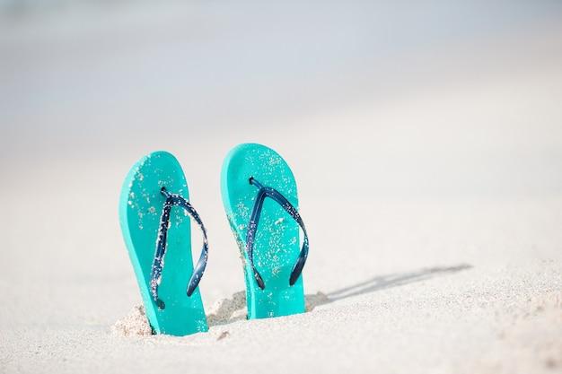 Sommer minze flip flops mit sonnenbrille am weißen strand