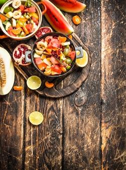 Sommer-nahrungsmittelsalat der tropischen früchte auf hölzernem hintergrund