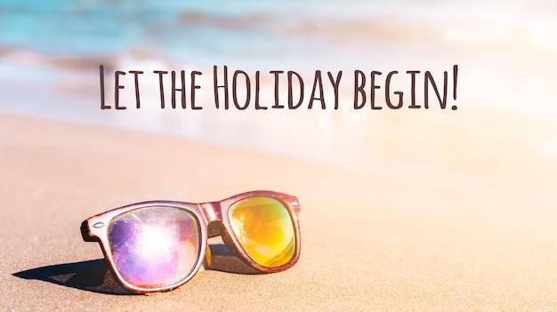 Sommer ocean beach urlaubskonzept mit sandküste und sonnenbrille. feiertagshintergrund mit text lassen sie den feiertag beginnen und sonnenlicht.