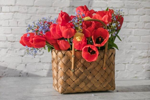 Sommer- oder frühlingsstrauß aus narzissen und roten tulpen in einem weidenkorb auf einer weißen oberfläche