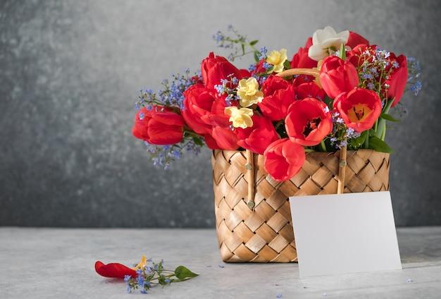 Sommer- oder frühlingsstrauß aus narzissen und roten tulpen mit rohling in einem weidenkorb auf einer weißen oberfläche