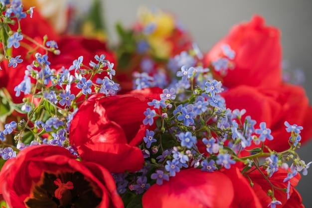 Sommer- oder frühlingsstrauß aus narzissen und roten tulpen