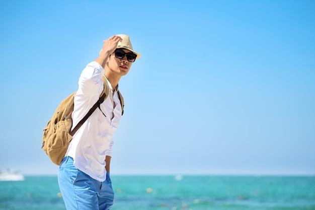 Sommer reise urlaub. mann trägt strohhut und sonnenbrille mit dem rucksack ralax, der an geht