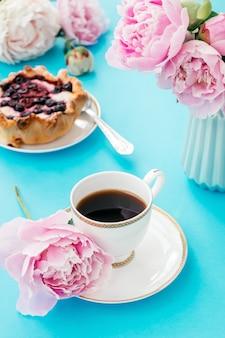 Sommer romantisches frühstück. tasse kaffee, kuchen, buch und pfingstrosen. guten morgen konzept.