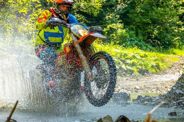 Sommer sonniger tag. viel spritzwasser verbirgt ein enduro-motorrad, wenn ein sportler einen waldbach überwindet. nahaufnahme