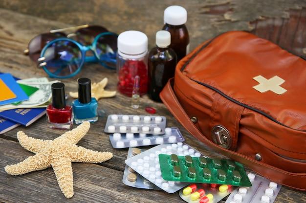 Sommer-strandzubehör für frauen für ihren seeurlaub und erste-hilfe-kasten auf altem holztisch. konzept der auf der reise benötigten medikamente. draufsicht. flach liegen.
