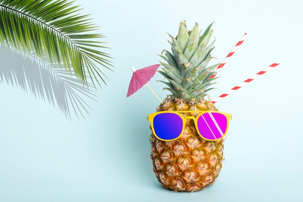 Sommer tropische ananas hintergrund ananas in sonnenbrille unter einer palme auf blauem hintergrund cocktailparty am strand ruhe entspannung und sommerkonzept hochwertiges foto