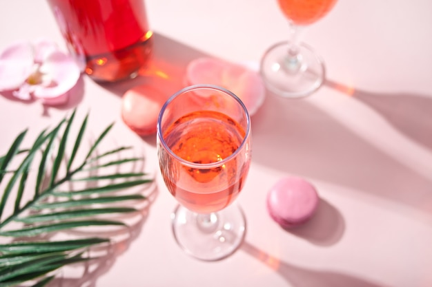 Sommer tropischer rosa cocktail verzierte rosa orchideenblumen, makronen und palmblatt.