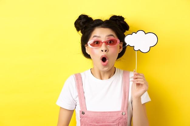 Sommer- und modekonzept. aufgeregtes partygirl in sonnenbrille, hält kommentarwolkenpartymaske und schnappt erstaunt nach luft, steht beeindruckt auf gelb.
