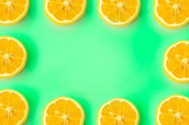 Sommer- und vitaminhintergrundrahmen. zitrone auf einem grünen hintergrund, minimales lebensmittelkonzept