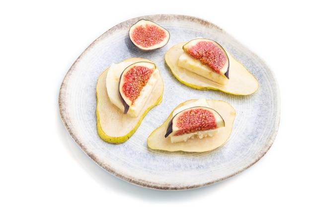 Sommer vorspeise mit birne, quark, feigen und honig auf keramikplatte