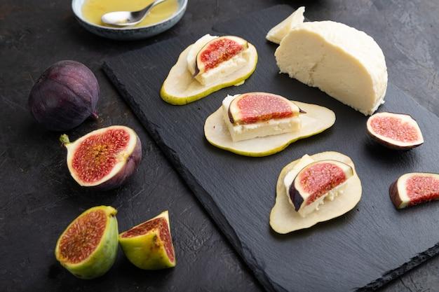 Sommer vorspeise mit birne, quark, feigen und honig auf schieferbrett