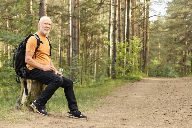 Sommer, wandern, aktiver lebensstil und alterskonzept. energetischer kaukasischer mann im ruhestand, der sommertag draußen in der wilden natur verbringt, zu fuß reist, ruhe auf stumpf mit flasche wasser hat