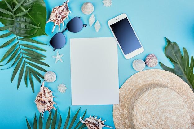 Sommer weibliches mode-outfit. sonnenhut, sonnenbrille, muscheln, geschenkboxen, smartphone mit tropischen palmenzweigen an der blauen wand. reisekonzept