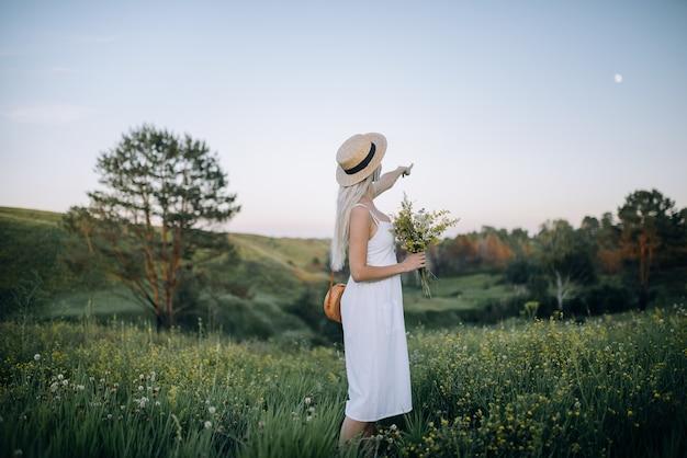 Sommerabend. ein junges mädchen in einem weißen kleid und einem strohhut steht auf einem schönen hang und zeigt auf den mond. wunderbare sommerzeit