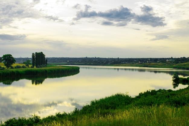 Sommerabenddämmerungs-himmelwolken dachten über einen see des wassers auf der küste mit bäumen des grünen grases und des waldes nach