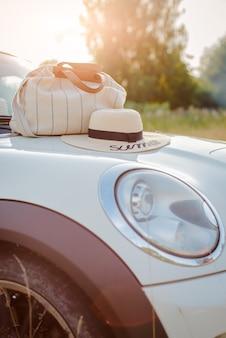 Sommeraccessoires liegen in der untergehenden sonne auf der motorhaube des autos.