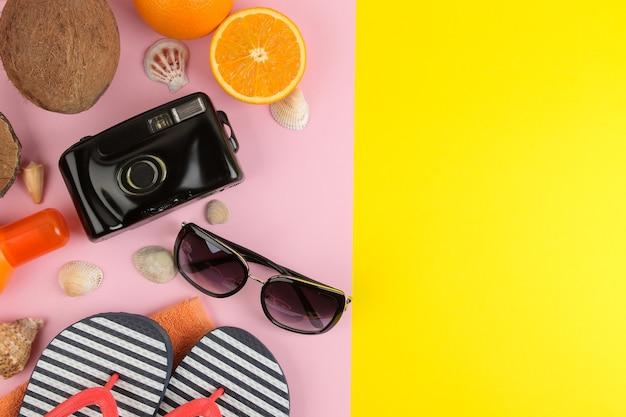 Sommeraccessoires mit sonnenbrille, hut, muscheln, flip-flops, kamera auf hellgelbem und rosa hintergrund. ansicht von oben.