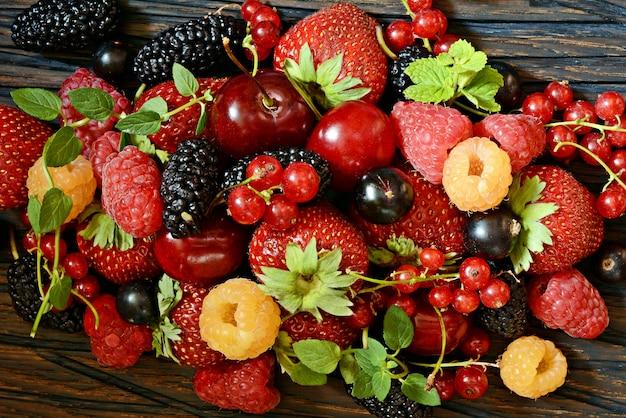 Sommerbeeren auf einer holzbrettnahaufnahme. beerenfrüchte wie erdbeeren, blaubeeren, rote johannisbeeren, himbeeren und brombeeren auf einem holzbrett.