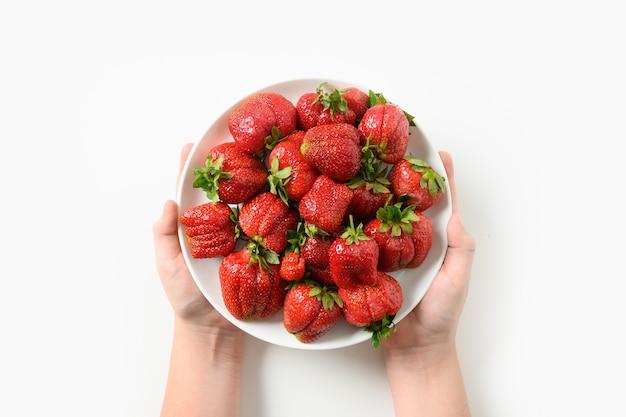 Sommerbeeren-dessert der organischen erdbeere in den kinderhänden auf weißem hintergrund konzept bio-öko-produkte.
