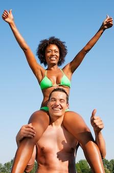 Sommerbikinimädchen, das auf schultern des mannes sitzt