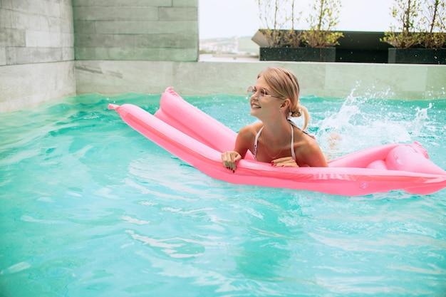 Sommerbild, das das sonnengebräunte mädchen schwimmt mit rosa matratze im pool und im lachen betäubt. trägt stilvollen weißen bikini und rosa sonnenbrille. lächeln und das leben genießen. sonnenbaden
