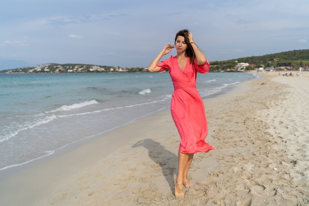Sommerbild der glücklichen sexy frau im herrlichen rosa kleid, das auf dem strand aufwirft. volle länge.