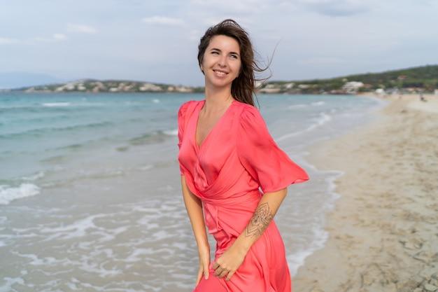 Sommerbild der glücklichen sexy frau im herrlichen rosa kleid, das auf dem strand aufwirft.