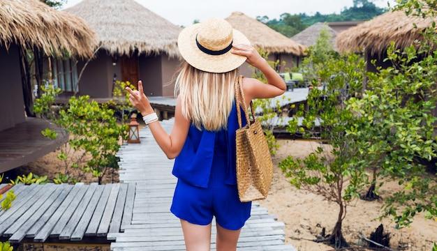 Sommerbild der jungen schönen frau im strohhut und im trendigen outfit, das in modernen stilvollen tropischen resorts aufwirft und frieden zeigt. blick von hinten. urlaub, sommerzubehör.