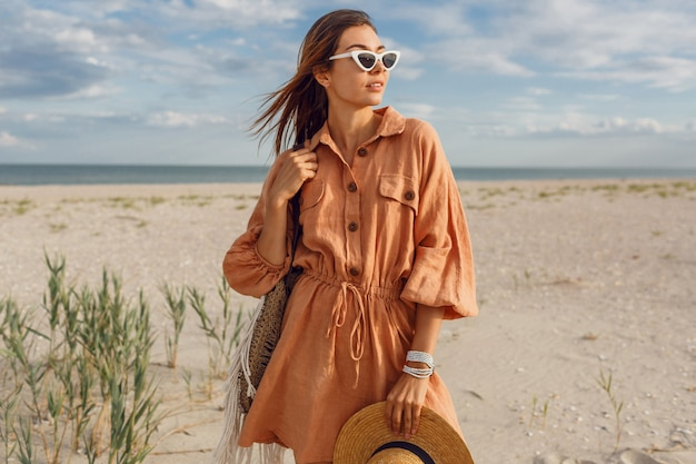 Sommerbild der schönen brünetten frau im trendigen leinenkleid, strohsack haltend. hübsches schlankes mädchen, das wochenenden nahe ozean genießt.