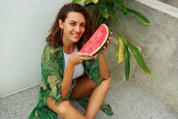 Sommerbild im freien der hübschen brünetten frau, die saftige wassermelone mit vergnügen isst.