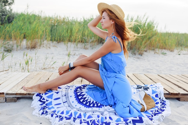 Sommerbild im freien der romantischen frau im strohhut, der am sonnigen strand im blauen kleid entspannt.