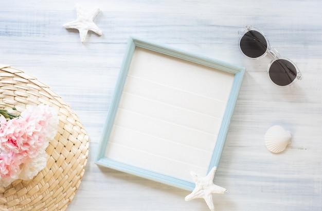 Sommerbilderrahmen mit sonnenbrille und muschel- und sternfisch- und blumendekoration auf hölzerner tabelle