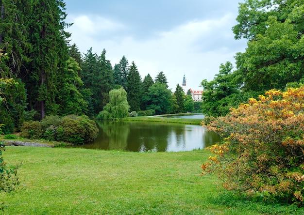 Sommerblick der burg pruhonice (prag, tschechien) mit seen und blühendem busch.