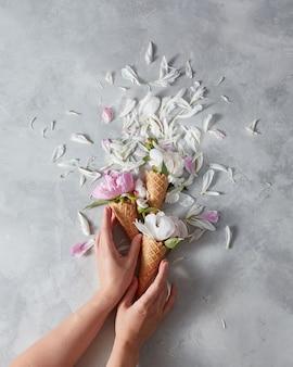Sommerblumen - frische zarte rosa und weiße pfingstrose in einem waffelkegel mit weiblichen händen, blütenblätter auf einem grauen marmortisch. platz für text, draufsicht.