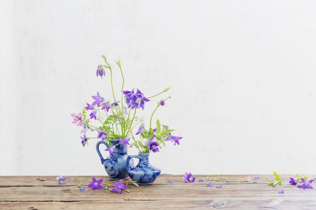 Sommerblumen im blauen krug auf altem holztisch