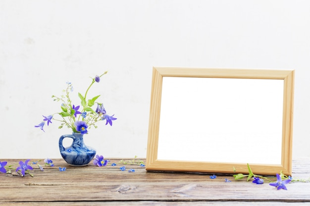 Sommerblumen im blauen krug und im holzrahmen auf altem holztisch