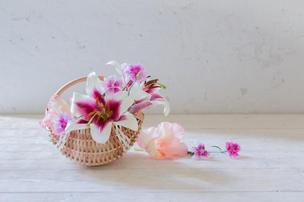 Sommerblumen im korb auf weißer oberfläche