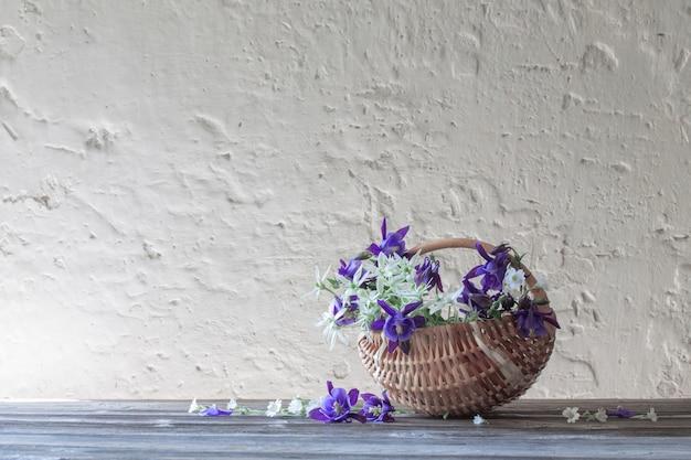 Sommerblumen im korb auf weißer wand