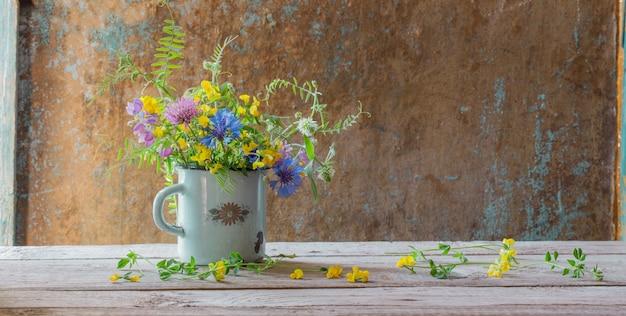 Sommerblumen in der alten tasse auf holztisch