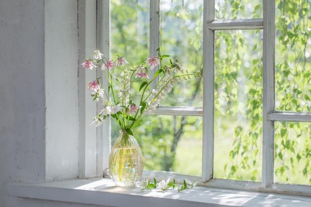 Sommerblumen in der vase auf der fensterbank im sonnenlicht