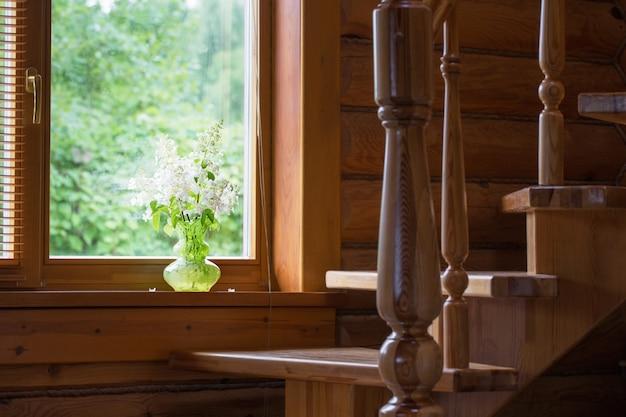 Sommerblumenstrauß in glasvase auf fensterbank im holzhaus